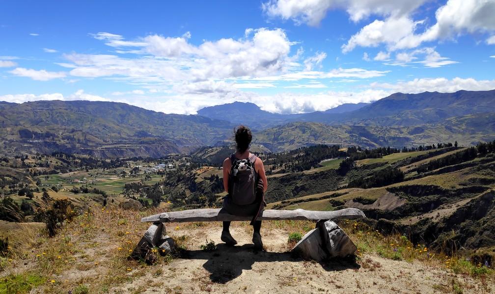 Salomé de dos, assise sur un banc et admirant la vue sur la campagne en Équateur