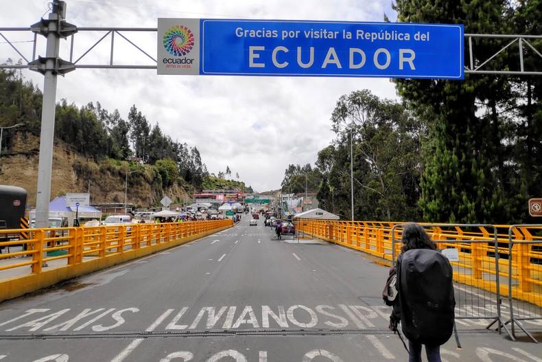 Salomé marche sous le panneau de frontière de l'Equateur