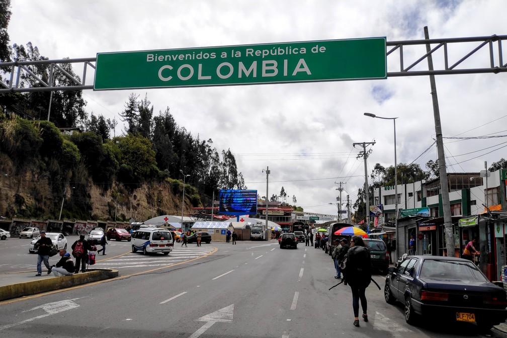 Salomé marche sous le panneau de frontière Colombien