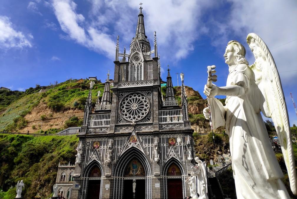 Église de Las Lajas à Ipiales avec une statue d'un ange blanc en premier plan