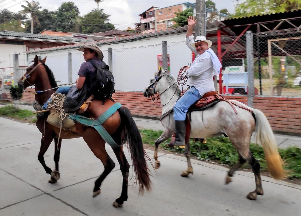 Deux hommes à cheval saluant les passants dans la rue à Salento