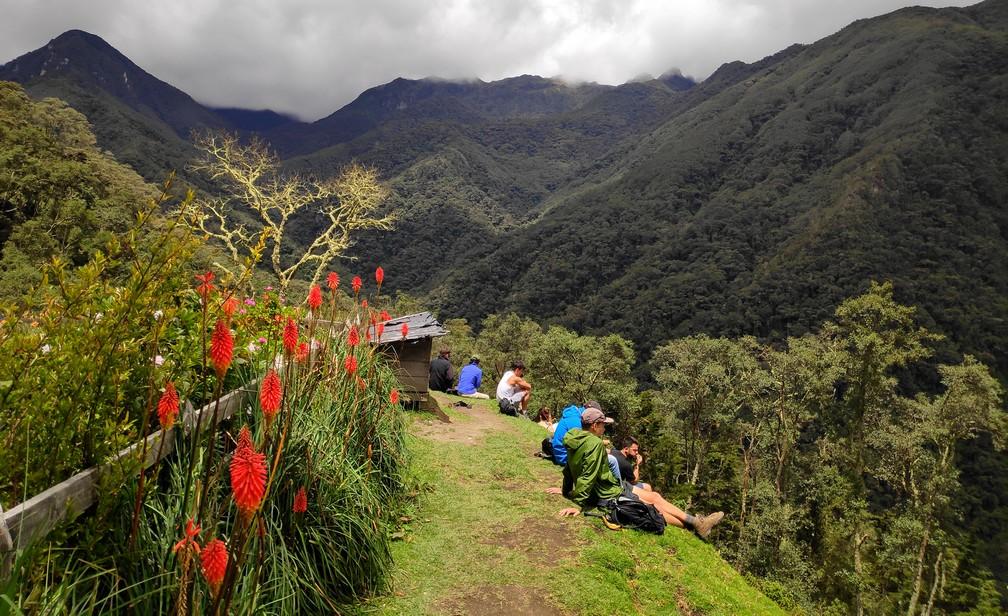 Vue sur les montagnes de la vallée de Cocora avec des randonneurs assis dans l'herbe au premier plan