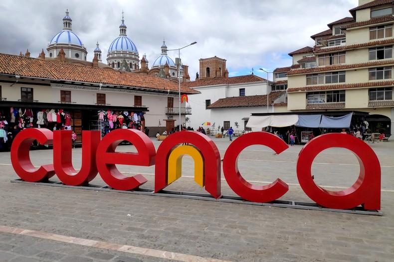 Cuenca écrit en grosses lettres rouges sur une place