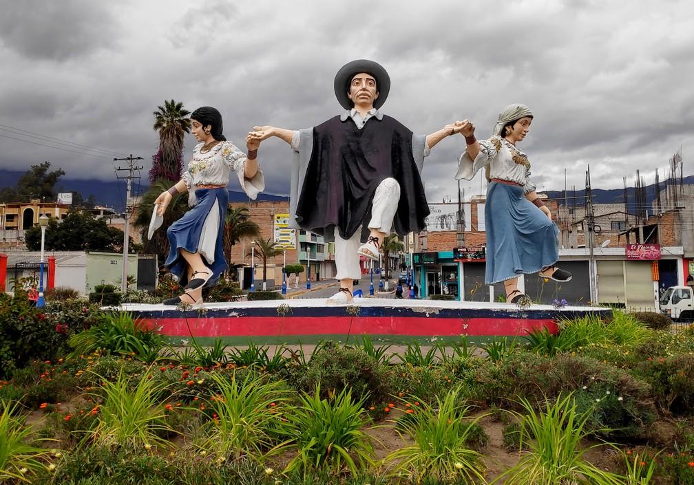 Statues d'Équatoriens en habit traditionnel dansant sur un rond point à Otavalo
