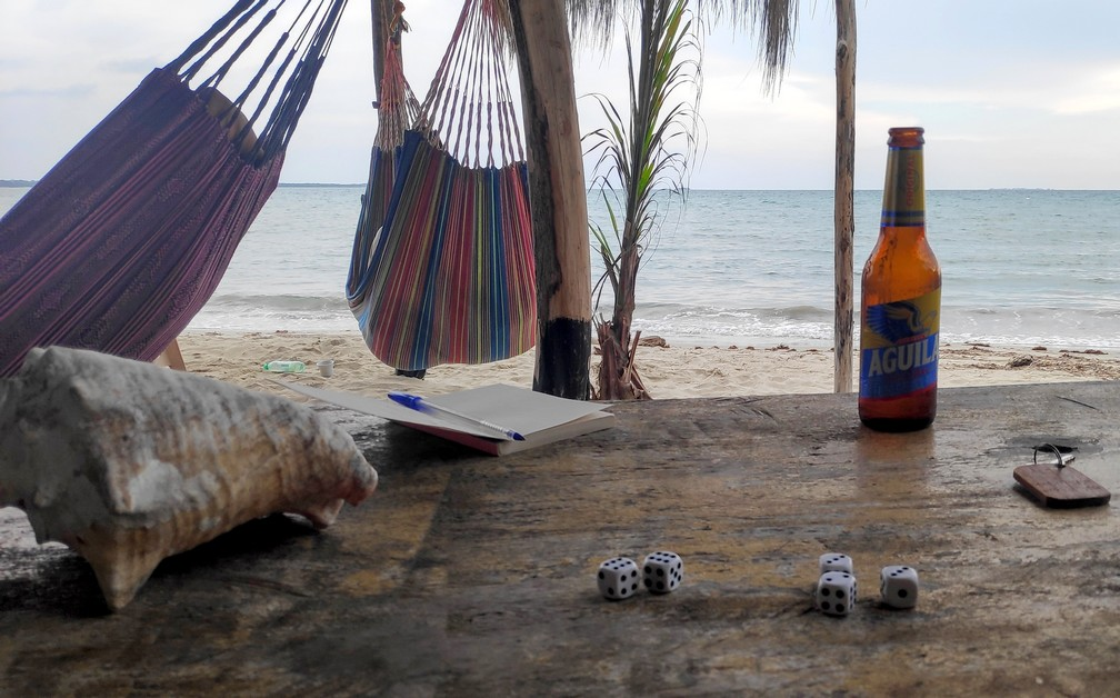 Hamacs avec vue sur la mer avec un set de dés et une bière sur une table en premier plan
