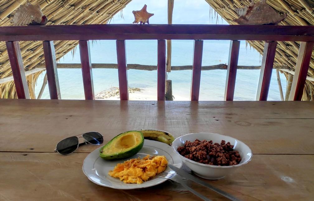 Oeufs brouillées, avocat, muesli et banane sur une table avec vue sur la mer en fond