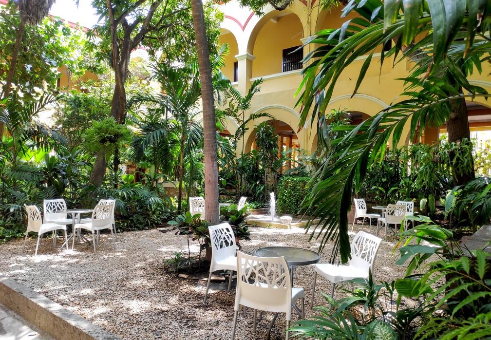 Patio typiquement colombien avec de la végétation et quelques tables et chaises