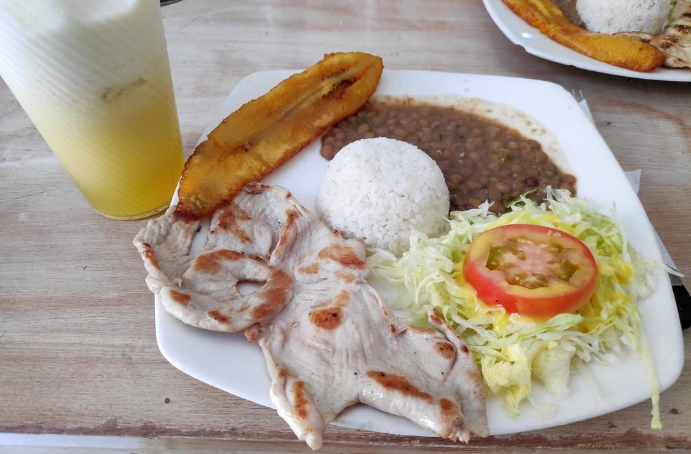 Banane plantain, salade, lentilles, riz et viande servis sur une assiette avec un jus de fruit