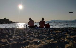 Couple assis plage Kitsilano Vancouver soleil couchant