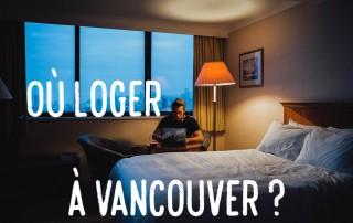 Homme assis à son PC dans une chambre d'hotel tamisée