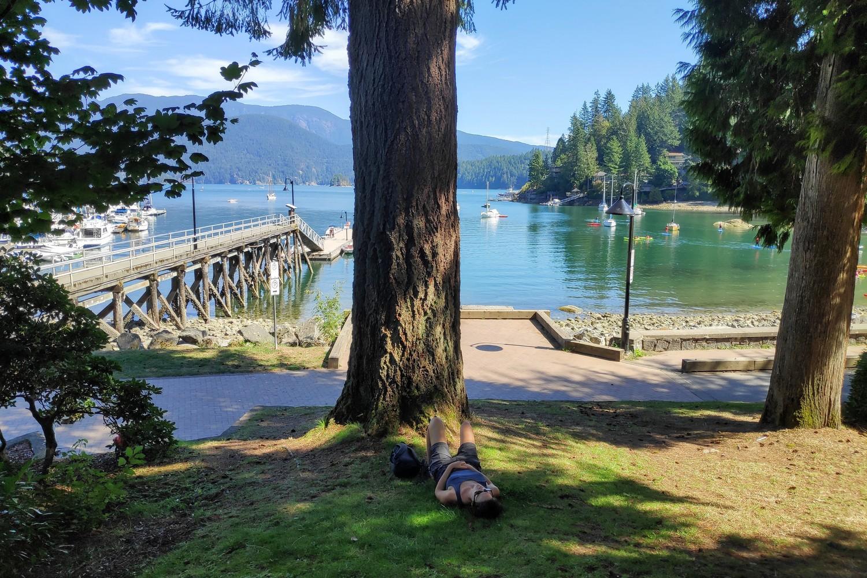 Salomé se repose à l'ombre d'un arbre devant la baie de Deep Cove