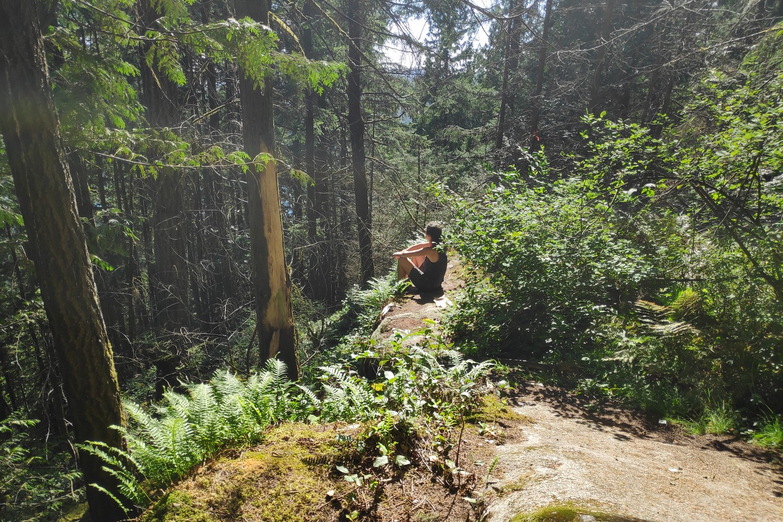 Salomé assise dans la forêt de Deep Cove